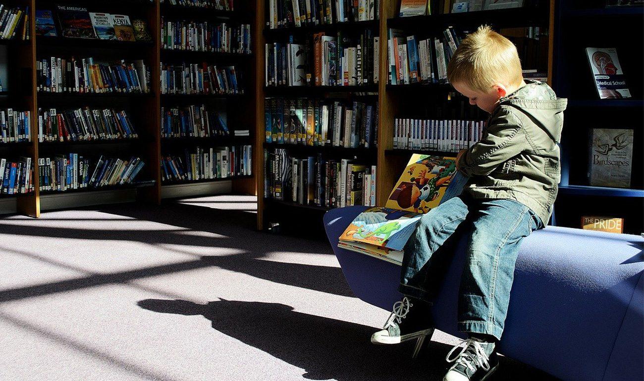 bambino che legge un libro di fiabe in una libreria